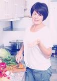 Mature woman making salad Stock Images