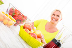 Mature woman making a smoothie Royalty Free Stock Photography