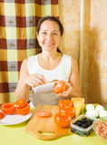 Mature woman making stuffed tomato Stock Image