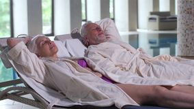 Aging couple relaxing on sunbeds by pool in hotel stock footage