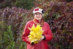 Mature woman with maple posy. Outdoor portrait of  mature woman with maple posy Royalty Free Stock Image