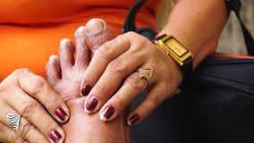 Mature woman massages foot of an old man. Close ups stock footage
