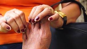 Mature woman massages foot of an old man. Close ups stock video