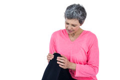 Mature woman massaging knee. While sitting against white background Royalty Free Stock Image