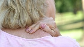 Mature woman massaging numb neck and shoulders, spine injury consequences. Stock photo stock image