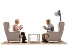 Mature woman and a mature man with cups sitting in armchairs Royalty Free Stock Photo