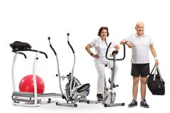 Mature woman and a mature man with exercising machines. Isolated on white background stock photo