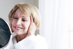 Mature Woman In The Mirror. Mature woman looking at herself in the mirror Stock Images