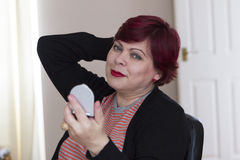 Mature woman with mirror indoors Royalty Free Stock Image