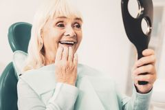 Mature woman with mirror looking at her denture. White smile. Close up of mature smiling woman holding mirror and viewing her new denture while touching her chin stock photos