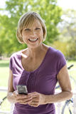 Mature woman with mobile phone, bicycle in background, smiling, portrait Stock Photos