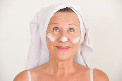 Mature Woman with moisturizer on face Stock Photography
