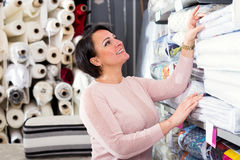Mature woman near bedspreads shelves. Portrait of cheerful women near bedspreads shelves in textile store royalty free stock image