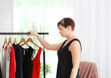 Mature woman near rack with small-sized clothes at home. Royalty Free Stock Photos