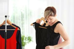 Mature woman near rack with small-sized clothes at home. Stock Photo