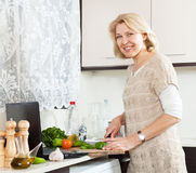 Mature woman  with notebook  cooking soup  in home's kitchen Royalty Free Stock Photos