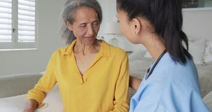 Mature woman and nurse. Front view close up of a mature mixed race woman talking with a young mixed race female nurse comforting her while sitting on a bed stock video footage