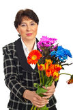 Mature woman offering flowers bouquet. Beauty mature woman offering flowers bouquet isolated on white background Royalty Free Stock Photography