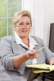 Mature woman offers card Stock Photos
