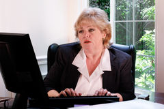 Mature woman in office typing Stock Images