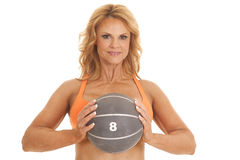 Mature woman orange bra medicine ball in front Stock Photo