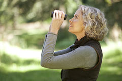 A mature woman outdoors, looking through a pair of binoculars Royalty Free Stock Image