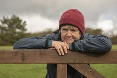 Mature woman outdoors. Resting on fence outdoors stock image