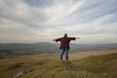 Mature woman with outstretched arms overlooking view. Mature woman with outstretched arms overlooking rural view royalty free stock photo