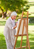 Mature woman painting royalty free stock photo