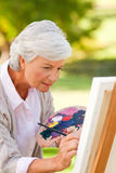 Mature woman painting in the park Stock Images
