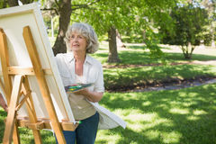 Mature woman painting in park Royalty Free Stock Photography