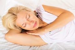 Mature woman in pajamas sleeping Stock Photos