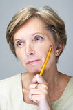 Mature woman with pencil Stock Images