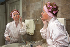 Mature Woman Performing Beauty Routine Royalty Free Stock Images