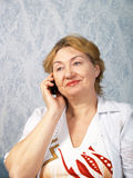 The mature woman with phone Stock Image
