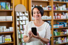 Mature woman with phone in drugstore Stock Image