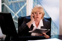 Mature woman on the phone at her desk Royalty Free Stock Photos