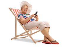 Mature woman with a phone sitting in a deck chair and looking at Royalty Free Stock Photography