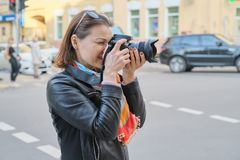 Mature woman with photo camera photographing on the street of spring city, female professional photographer,copy space stock images