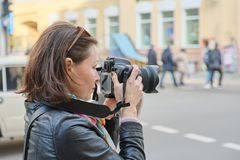 Mature woman with photo camera photographing on the street of spring city, female professional photographer,copy space stock image