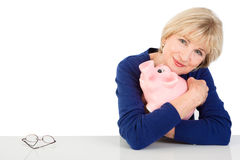 Mature woman with piggy bank Royalty Free Stock Images