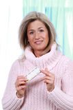 Mature woman with pill box. Mature woman points on tablet distributor Royalty Free Stock Photography