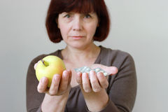 Mature Woman with Pills and Apple Stock Image
