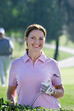 Mature woman in pink polo shirt and golf glove standing on golf course, holding putter, smiling, portrait Stock Images