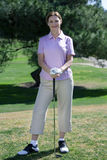 Mature woman, in pink polo shirt and golf glove, standing on golf course, leaning on golf club, smiling, front view, portrait Royalty Free Stock Image