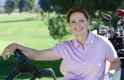 Mature woman, in pink polo shirt, sitting in golf buggy on golf course, smiling, side view, portrait Royalty Free Stock Photos