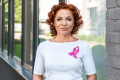 Mature woman with pink ribbon looking at camera breast cancer awareness concept stock images