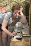 Mature Woman Playing Antique Wooden Piano in Desert Setting Stock Photo