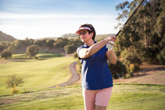 Mature woman playing golf Royalty Free Stock Images