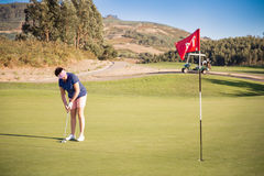Mature woman playing golf with putter club. On course. Golfer concentrating for putting on green. Beautiful sunny Landscape, green hills, blue sky. Portugal stock photos